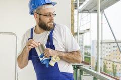 O trabalhador da construção em um equipamento do trabalho e em um capacete na cabeça desaparafusa com cuidado uma garrafa do álco Fotos de Stock