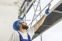 O trabalhador da construção em um vestuário do trabalho, em umas luvas protetoras e em um capacete na cabeça dá uma espátula Trab Fotos de Stock