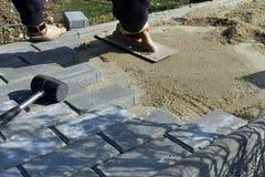 O trabalhador da construção está colocando a pedra do pavimento concreto para o trabalho do passeio no canteiro de obras O trabal foto de stock royalty free