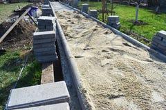 O trabalhador da construção está colocando a pedra do pavimento concreto para o trabalho do passeio no canteiro de obras O trabal imagem de stock royalty free