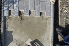 O trabalhador da construção está colocando a pedra do pavimento concreto para o trabalho do passeio no canteiro de obras O trabal fotos de stock