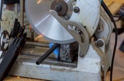 O trabalhador da construção está cortando a barreira de aço dos trilhos de aço do metal fotografia de stock
