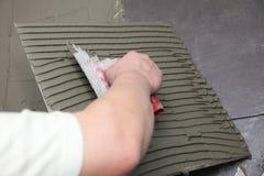 O trabalhador da construção está telhando em casa o adesivo do assoalho de telha fotografia de stock royalty free