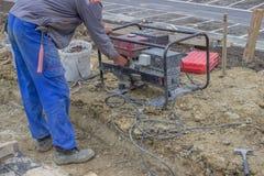 O trabalhador da construção liga o gerador bonde portátil 2 fotos de stock