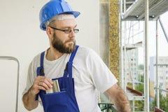 O trabalhador da construção mau no equipamento de trabalho e no capacete está em uma alta altitude em um canteiro de obras com pl Imagem de Stock
