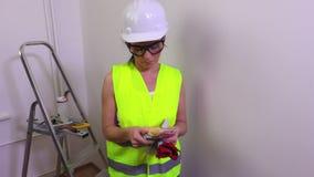 O trabalhador da construção da mulher que contam o dinheiro e as mostras manuseiam para baixo vídeos de arquivo