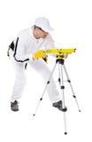 O trabalhador da construção nas combinações brancas nivela a ferramenta Foto de Stock Royalty Free
