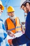 O trabalhador da construção no uniforme protetor que discute a construção planeia com homem de negócios imagens de stock