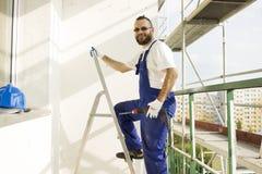 O trabalhador da construção no vestuário do trabalho e em luvas protetoras entra em uma escada com uma broca à disposição Imagem de Stock Royalty Free