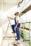 O trabalhador da construção no vestuário do trabalho e em luvas protetoras entra em uma escada com uma broca à disposição Fotos de Stock Royalty Free