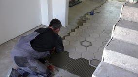 O trabalhador da construção pôs telhas do hexágono sobre o assoalho O Tiler instala telhas da faiança vídeos de arquivo