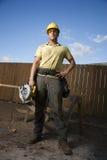 O trabalhador da construção que está com viu Fotografia de Stock Royalty Free