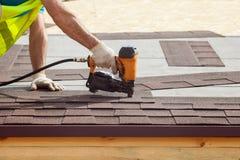 O trabalhador da construção que põe as telhas do telhado de asfalto com prego atira em uma casa de quadro nova