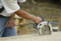 O trabalhador da construção que usa uma circular viu foto de stock