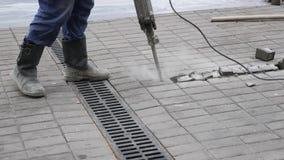 O trabalhador da construção remove a telha concreta com a máquina de perfuração do jackhammer fora video estoque
