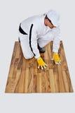 O trabalhador da construção verifica um assoalho de madeira Foto de Stock Royalty Free