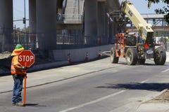 O trabalhador da estrada em uma veste alaranjada mostra uma parada do sinal de estrada Imagens de Stock