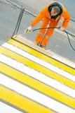 O trabalhador da estrada que pinta e que observa linhas do cruzamento pedestre no asfalto surge imagem de stock royalty free