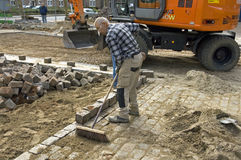 O trabalhador da estrada varre a areia entre pedras Fotos de Stock