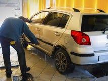 O trabalhador da lavagem de carros lava um carro Fotos de Stock