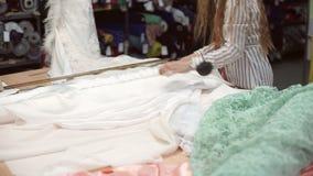O trabalhador da loja da tela desempacota o tecido branco do atlas do rolo dentro video estoque