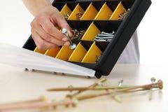 O trabalhador da mão escolhe os parafusos da caixa, fim de uma porca acima Fotografia de Stock Royalty Free