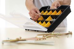 O trabalhador da mão escolhe um parafuso da caixa, fim acima Fotos de Stock Royalty Free