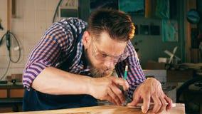 O trabalhador da obra de carpintaria marca a madeira com lápis Carpinteiro, trabalho do artesão vídeos de arquivo
