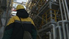 O trabalhador da opinião da parte traseira anda entre o sistema de encanamento da refinaria de petróleo