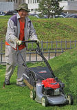 O trabalhador da rua está cortando o gramado Imagens de Stock