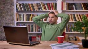 O trabalhador de escritório que senta-se na frente do portátil fica nervoso e forçado sobre a falha do erro Estantes no filme
