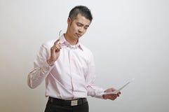 O trabalhador de escritório asiático lê uma mensagem Imagens de Stock Royalty Free