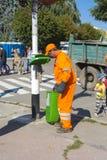O trabalhador de serviço público remove o lixo do tanque completo Dia do th Imagens de Stock Royalty Free