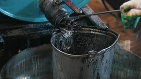 O trabalhador derrama o líquido do óleo ou do produto químico de motor na cubeta riscada velha video estoque