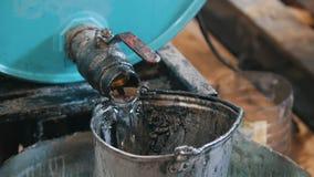 O trabalhador derrama o líquido do óleo ou do produto químico de motor na cubeta riscada velha vídeos de arquivo
