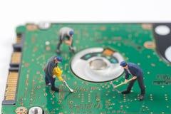 O trabalhador diminuto está escavando um furo no varrão eletrônico do disco rígido imagens de stock royalty free