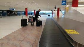 O trabalhador do aeroporto recolhe bagagem perdida do transporte filme