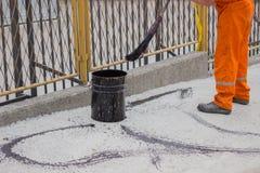 O trabalhador do asfalto aplica o revestimento de aderência (emulsão do betume) com uma vassoura 4 foto de stock royalty free
