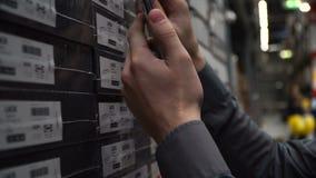 O trabalhador do cliente do homem com smartphone escolhe procura bens da caixa no armazém da loja vídeos de arquivo