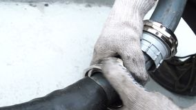 O trabalhador do close up nas luvas gerencie a alavanca para conectar a tubulação de borracha filme