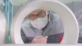 O trabalhador do close up nos vidros e na máscara verifica a qualidade das linhas da fibra de vidro video estoque