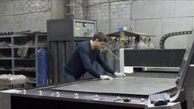 O trabalhador do coordenador ajusta a folha do ferro cortando a placa de metal na máquina do laser do CNC filme