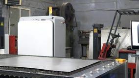 O trabalhador do coordenador ajusta a folha do ferro cortando a placa de metal na m?quina do laser do CNC filme