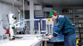 O trabalhador do equipamento de impressão, ajusta, regula o processo de impressão processo de trabalho de pacotes da impressão pa vídeos de arquivo