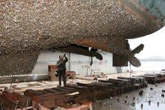 O trabalhador do estaleiro limpa a água do stuya do navio Imagens de Stock Royalty Free