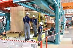 O trabalhador do grupo monta um transformador na engenharia mecânica - fotografia de stock royalty free