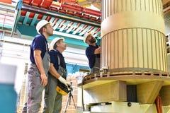 O trabalhador do grupo monta um transformador na engenharia mecânica - imagem de stock royalty free