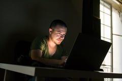 O trabalhador do Internet está em seu portátil que escuta a música na obscuridade imagens de stock