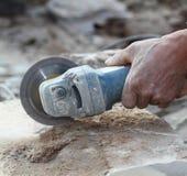 O trabalhador do moedor corta uma pedra a ferramenta elétrica Imagem de Stock
