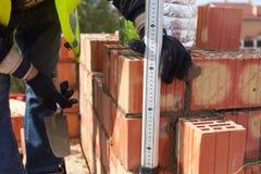 O trabalhador do pedreiro da construção mede a espessura das emendas no tijolo Fotografia de Stock